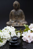 Stack of stones with blossoms and buddha Royalty Free Stock Images