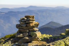 Stack of stones covered with moss on top of a mountain on mountains background. Concept of balance and harmony. Stack of zen rocks. Wild nature and geology Royalty Free Stock Photo