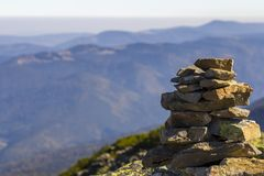 Stack of stones covered with moss on top of a mountain on mountains background. Concept of balance and harmony. Stack of zen rocks. Wild nature and geology Stock Photo