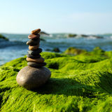 Stack of stones, pebble balance at beach. Amazing stack of stones on green moss at seaside beach, group of pebble balance on large rock as meditation, concept Stock Photos
