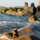 Stack of stones, pebble balance at beach. Amazing stack of stones at seaside beach, group of pebble balance on large rock as meditation, concept for Zen or Stock Photo