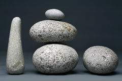 Stack of stones - pebbles on dark grey background Royalty Free Stock Images