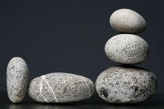 Stack of stones - pebbles on dark grey background Royalty Free Stock Photos