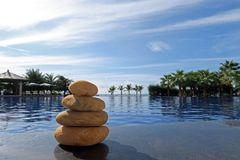 Stack of stones on pool edge Royalty Free Stock Image
