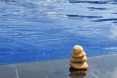 Stack of stones on pool edge Royalty Free Stock Photo