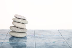Stack of stones for spa procedures on a table made of tiles Stock Photography