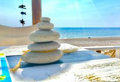 Stack of stones. Stack of zen like stones with blue sea background in a table with texture. A concept of spa, freedom, relaxation, inspiration, balance and stock images