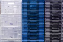 Stack Storage of new colourful white, grey and blue plastic container boxes royalty free stock image