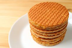 Stack of Stroopwafel on the White Plate. Served on Wooden Table Royalty Free Stock Photography