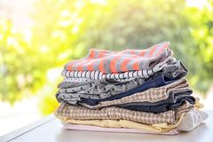 Stack of stylish child clothes on table. Against blurred background royalty free stock images