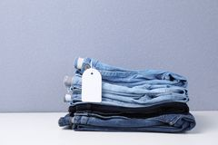 Stack of stylish jeans with tag. On table stock image