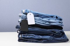 Stack of stylish jeans with tags. On table royalty free stock photos
