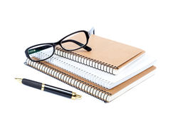 Stack stylish notebook, pen and glasses. Royalty Free Stock Images