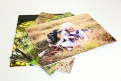 Stack of Styrene Mounted Family Portrait Prints on White Background. A stack of styrene mounted family portrait prints is laying on a white background, with a stock photography