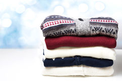 A stack of sweaters on the wooden background. Stock Photos