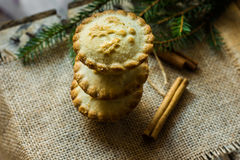 Stack of sweet mince pies on sackcloth on wood box with cinnamon sticks and fir tree branches Stock Image