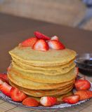 Stack of sweet pancakes with fresh strawberries and icing sugar Royalty Free Stock Photos