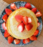 Stack of sweet pancakes with fresh strawberries and icing sugar Stock Photos