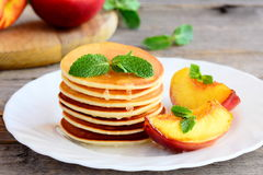 Stack of sweet pancakes with syrup and grilled nectarines slices on a serving plate. Simple pancake recipe. Pancakes with maple syrup recipe. Pancakes recipe Royalty Free Stock Photography