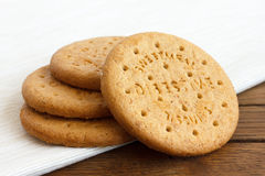 Stack of sweetmeal digestive biscuits on dark wood and napkin. Royalty Free Stock Photo