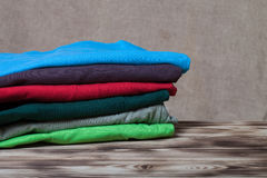 Stack of T-shirts on wooden table opposite a defocused burlap ba Royalty Free Stock Photo