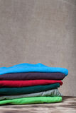 Stack of T-shirts on wooden table opposite a defocused burlap ba Stock Image