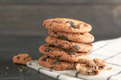 Stack of tasty chocolate chip cookies on napkin. And wooden background royalty free stock images