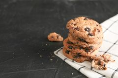 Stack of tasty chocolate chip cookies on napkin and wooden background. Space for text stock photos