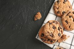 Stack of tasty chocolate chip cookies on napkin and wooden background, top view. Space for text stock photos