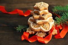 Stack of tasty gingerbread cookies, ribbon and Christmas tree branch on wooden background, close up Stock Image