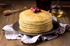 Stack of Tasty Homemade Pancakes with Cranberries and Honey Cup of Berries Tea Wooden Background Famale Hand Stock Image