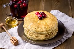 Stack of Tasty Homemade Pancakes with Cranberries and Honey Cup of Berries Tea Wooden Background Famale Hand Top View Above Stock Images