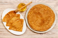Stack of tasty pancakes with honey in jar on wooden bachground.  Royalty Free Stock Photo