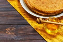 Stack of tasty pancakes with honey in jar on wooden bachground.  Stock Photography