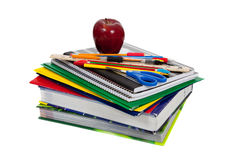 Stack of textbooks with school supplies on top. A stack of textbooks with school supplies including an apple, pencils, pens, a ruler, colored pencils, scissors royalty free stock photos