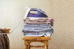 A stack of textile bed sheets blankets with iron on top f stock photography