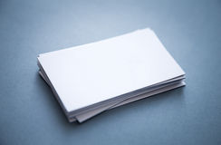 Stack of thick blank business cards. Thick blank business cards stacked up on a grey background with blurred (bokeh) front and back corners Royalty Free Stock Photography