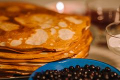 A stack of thin Russian hot pancakes blini  with currants. stock photos