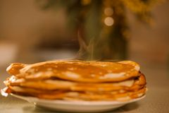 A stack of thin Russian hot pancakes blini  with steam emanating from them. Shrovetide Maslenitsa - traditional Russian holiday royalty free stock image