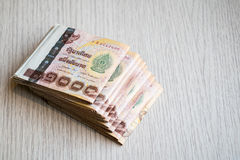 Stack of thousand bath Thai money on wooden table Stock Photography