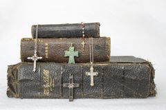 Antique Worn Leather Bibles with Antique to Modern Crosses on White Background. Stack of Three Antique Leather Bibles with Collection of Crosses Ranging from stock photo