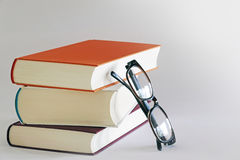 Stack of three books with reading glasses Stock Photography