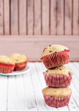 A stack of three cupcakes. On the wooden table royalty free stock photo