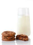 Stack of three homemade chocolate chip cookies, halves of cookies and glass of milk Royalty Free Stock Photos