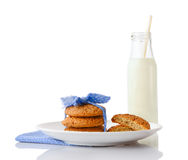 Stack of three homemade oatmeal cookies on plate and bottle of milk Royalty Free Stock Photos