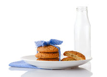 Stack of three homemade oatmeal cookies on plate and empty milk bottle Stock Photography