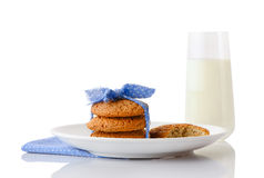 Stack of three homemade oatmeal cookies tied with blue ribbon in small white polka dots and bitten cookie on white ceramic plate o Royalty Free Stock Images