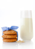 Stack of three homemade oatmeal cookies tied with blue ribbon in small white polka dots, ear of oats and glass of milk Royalty Free Stock Image