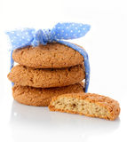 Stack of three homemade oatmeal cookies tied with blue ribbon in small white polka dots and half of cookie Royalty Free Stock Photo
