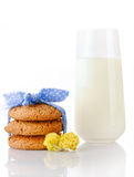 Stack of three homemade oatmeal cookies tied with blue ribbon in small white polka dots, tiny yellow flowers and glass of milk Royalty Free Stock Images